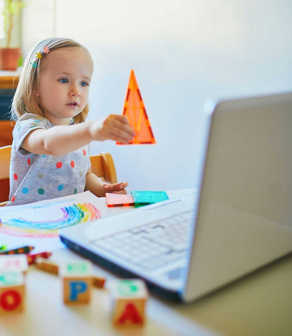 Math Games - Child holding up triangle to computer screen.